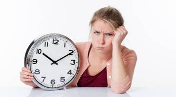 complaining beautiful young blond woman holding a clock